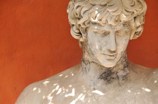 주황색 안뜰에있는 그리스 조각의 머리