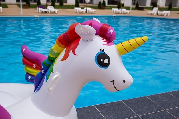 푸른 물이 있는 수영장에서 풍선 유니콘의 머리