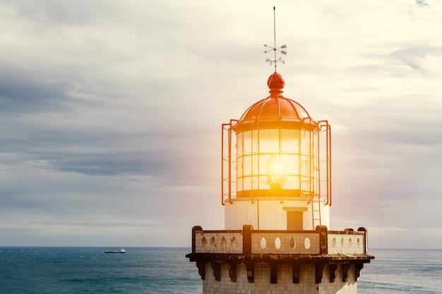 ランプがオンになっている古いヴィンテージ灯台の頭