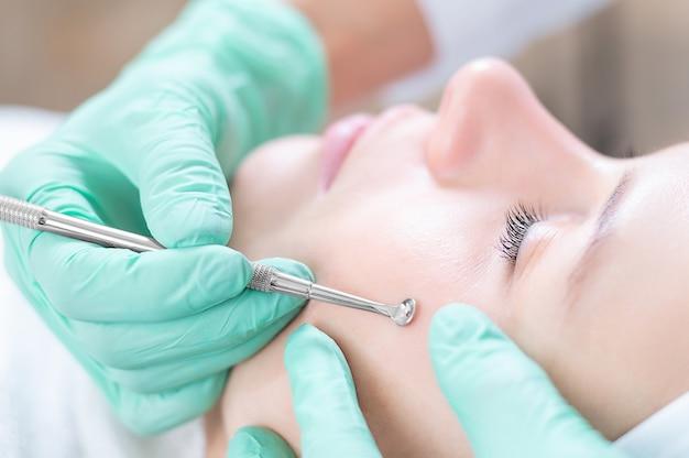 Голова женщины, лежащей на диване в белой кепке в косметологической клинике с закрытыми глазами и улыбкой. доктор держит ложку uno возле ее лица. смешанная техника