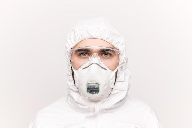 保護眼鏡、人工呼吸器、白いつなぎ服を着た若い男性の臨床医または科学者の頭