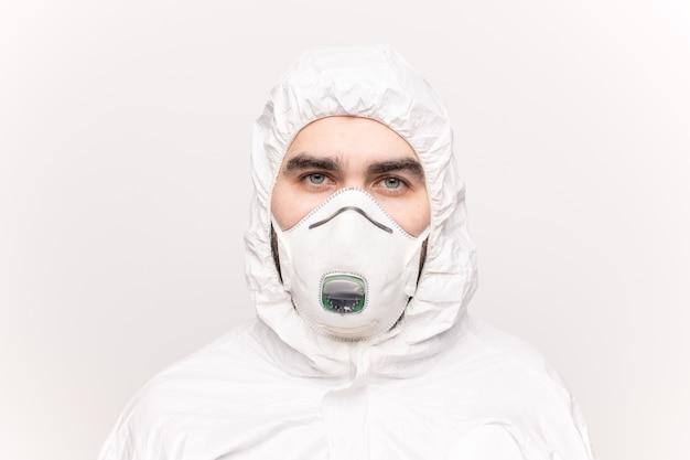 呼吸器と白い保護カバーオールを身に着けている青い目を持つ若い男の頭