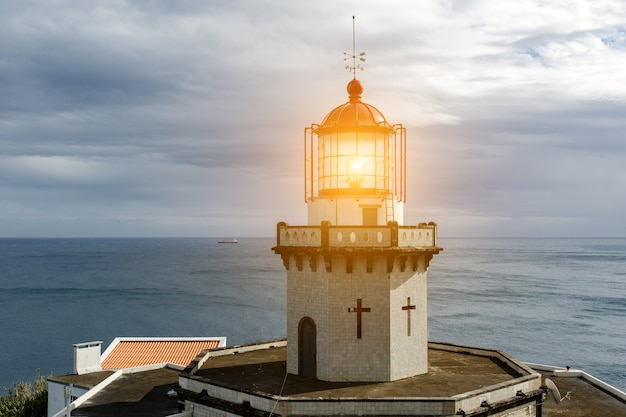 Head of old vintage lighthouse with turned on lamp