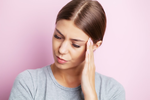 Head pain, exhausted young woman has suffering from unbearable headache
