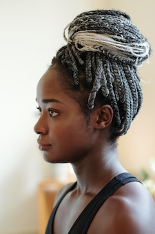 Head of pensive young black woman with braided hair in bun looking in front of her