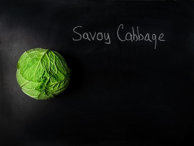 Head of savoy cabbage on black board with incription