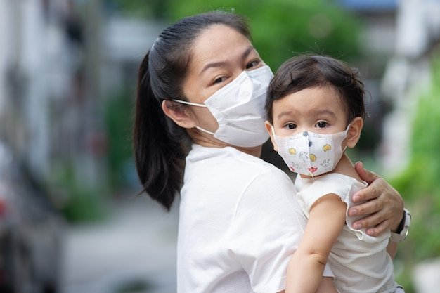 Head shot of asian mother wearing white face mask holding her little toddler baby girl who is her daughter wear baby face mask, they look at camera, covid-19 concept