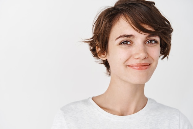 Head shot of beautiful natural woman with short hair, smiling and looking happy, wearing t-shirt, standing against white wall