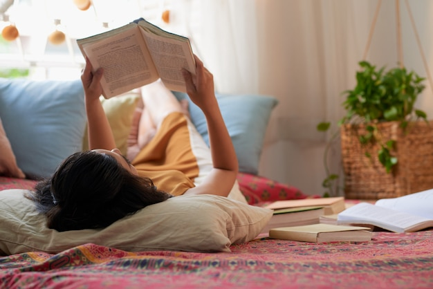 Over the head shot of brunette lying in bed reading a book