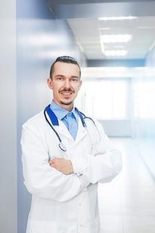 ヘッドショットは、笑顔の男性医師セラピストを閉じます。病院のホールで聴診器で若い医者