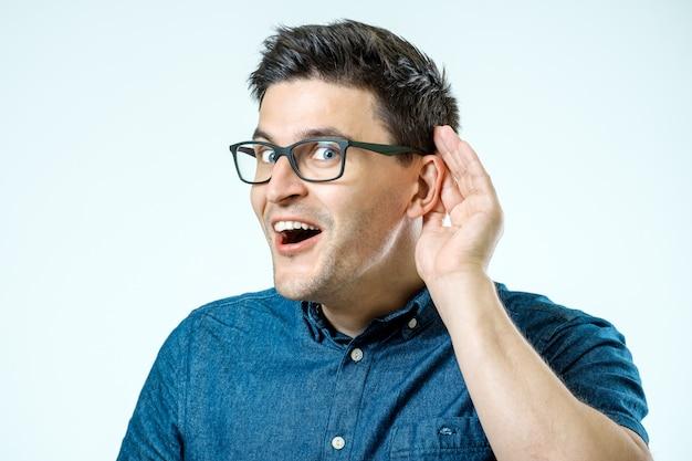 Head shot of man trying listen gossip or news.
