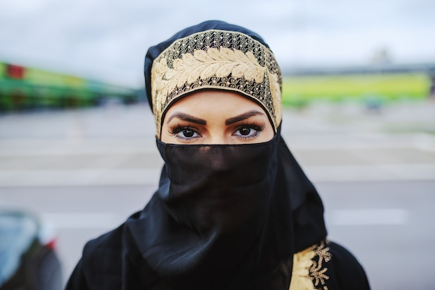 Head shot of mysterious attractive muslim woman in traditional wear standing outdoors.