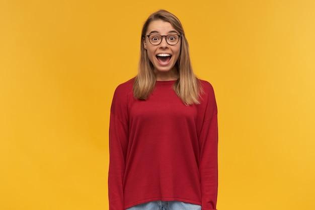 Снимок головы смешной счастливой радостной молодой блондинки в очках, широко улыбающейся, сияющей от счастья, полностью удовлетворенной, одетой в красный свитер, очки