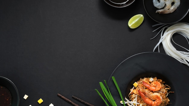 Over head shot of pad thai, stir fly of thai noodle with shrimp, egg and ingredients in black ceramic plate on black table