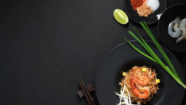 Over head shot of pad thai, stir fly of thai noodle with shrimp, egg, ingredients and seasoning in black ceramic plate on black table