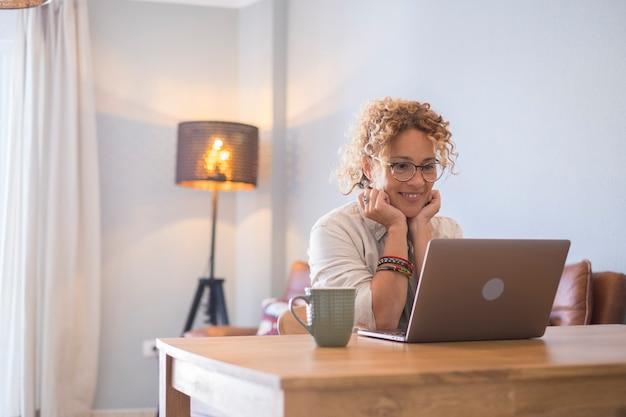 Голова выстрелил приятный счастливый фрилансер молодой женщины, работающий на компьютере дома. привлекательная деловая женщина учится в интернете, использует программное обеспечение для ноутбуков, просматривает информацию в интернете или делает покупки в интернет-магазине.