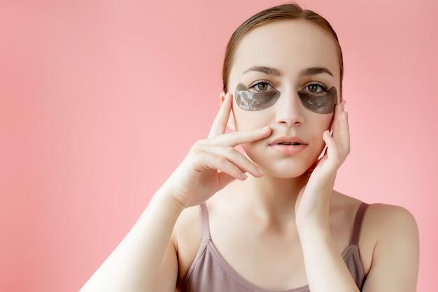 헤드 샷 초상화는 피부 관리 절차를 즐기는 카메라를 바라보는 눈 아래 보습 패치 마스크로 웃는 젊은 여성을 닫습니다.