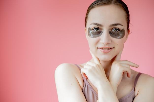 헤드 샷 초상화는 스킨 케어 절차를 즐기는 카메라를보고 눈 보습 패치 마스크 아래 웃는 젊은 여자를 닫습니다.