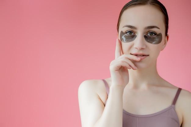 Портрет выстрел в голову крупным планом улыбается молодая женщина с увлажняющей маской пятен под глазами, глядя на камеру, наслаждаясь процедурой по уходу за кожей.