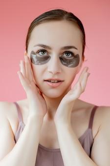 ヘッドショットの肖像画は、目の下の保湿パッチマスク探しで笑顔の若い女性をクローズアップ