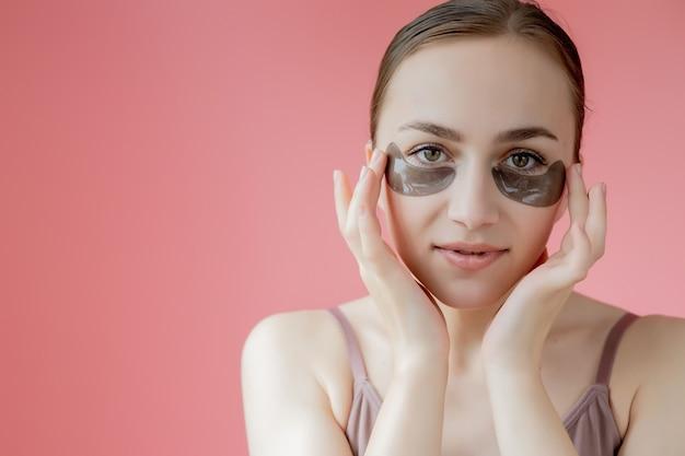 헤드 샷 초상화는 눈 아래 보습 패치와 함께 웃는 젊은 여자를 닫습니다