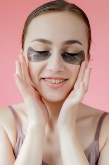 헤드 샷 초상화는 눈 아래 보습과 웃는 젊은 여자를 닫습니다