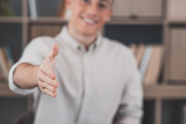 Head shot portrait smiling businessman wearing glasses extending hand for handshake at camera, friendly hr manager greeting candidate on interview, offering deal, welcoming client at meeting