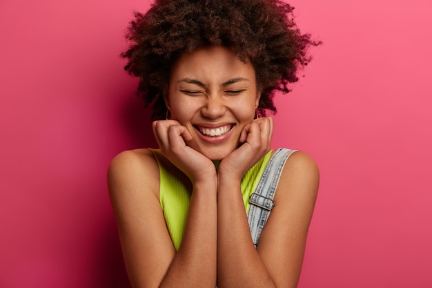 Head shot of positive curly haired woman keeps hands under chin, closes eyes and smiles broadly, enjoys nice time in good company, dressed in fashionable clothes, isolated on pink wall