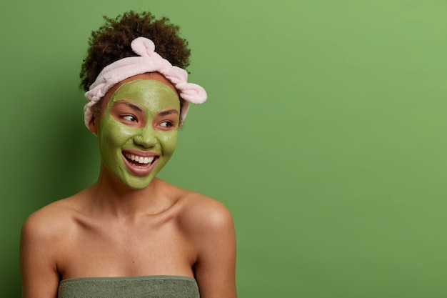 Head shot of smiling carefree woman has bare shoulders, looks away with pleasure, does skin care beauty facial routine, wears green mask on face, headband, isolated over  wall with blank space