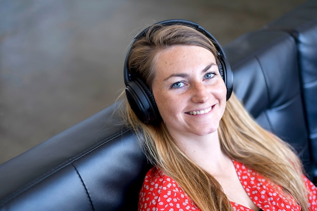 A head and shoulder shot of a woman looking into the camera with headphones
