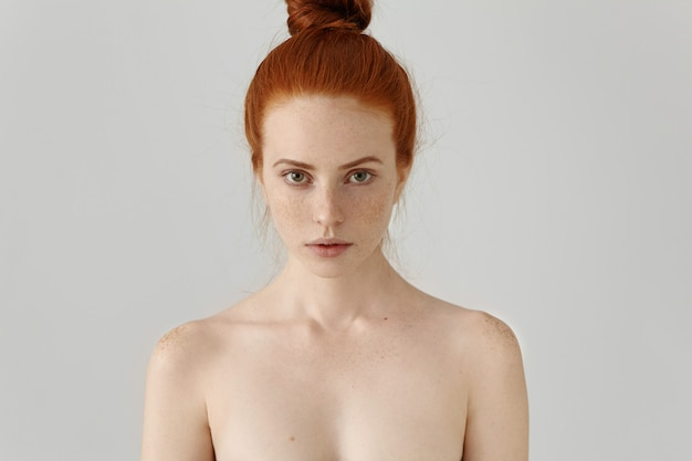 Head and shoulders of attractive young female model with ginger hair bun and freckles posing topless at blank wall. beauty and skincare concept.