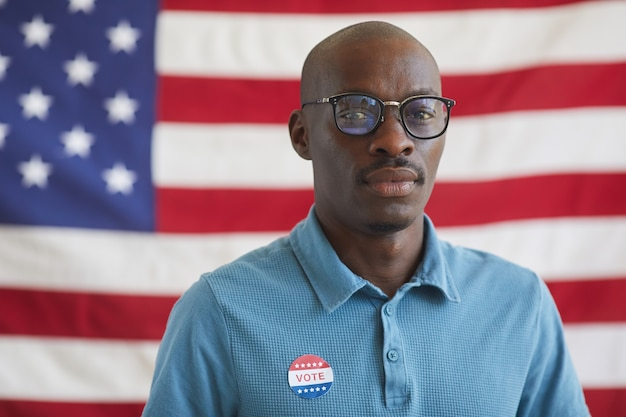 Head and shoulders portrait of bald african-american man with vote sticker  while standing against american flag on election day, copy space