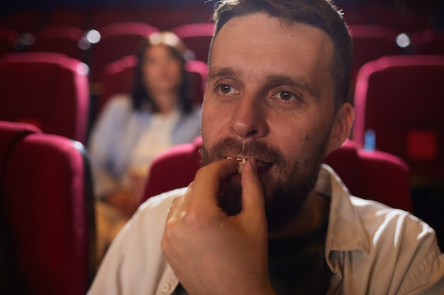 Head and shoulders portrait of mature man eating popcorn in cinema while enjoying movie alone, copy space