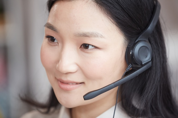 Head and shoulders portrait of smiling asian woman wearing headset and talking to customer while working in call center or support service