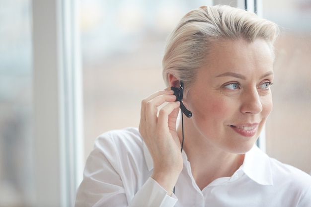 Head and shoulders portrait of smiling businesswoman wearing headset and looking at window while working in call center