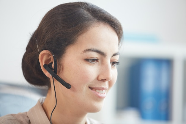 Head and shoulders portrait of smiling young woman wearing headset and talking to customer while working in call center or support service