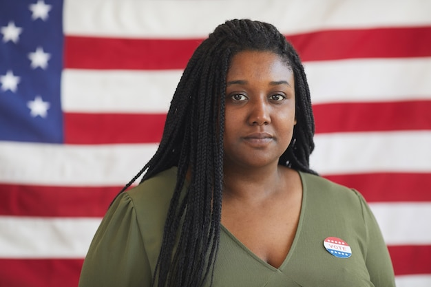 Head and shoulders portrait of young african-american woman with vote sticker  while standing against american flag on election day, copy space
