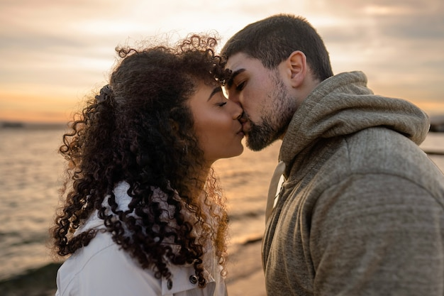 Head and shoulders portrait of young beautiful couple in love kissing at sunset in winter seaside resort with cloudy sky.