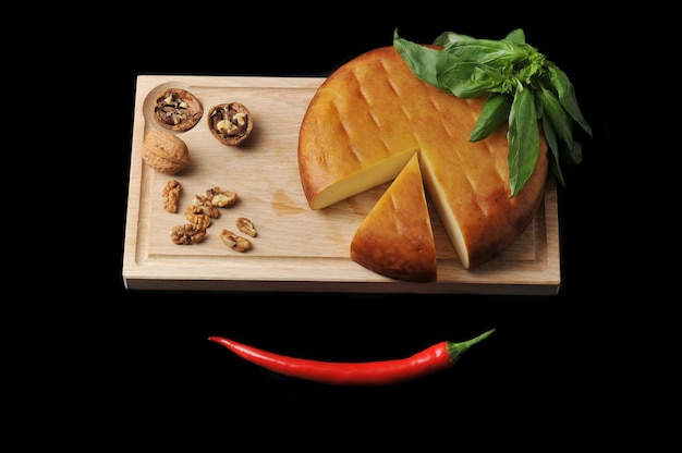 Head of smoked suluguni cheese on wooden board with walnuts and basil on black surface