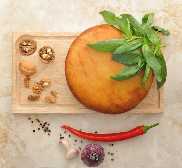 Head of smoked suluguni cheese on wooden board with walnuts and basil on the marble surface