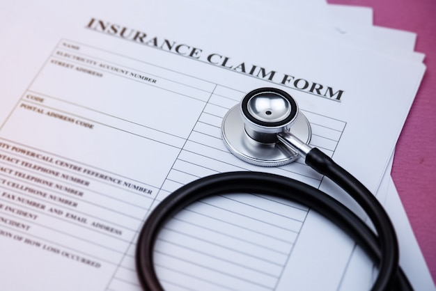 Head of stethoscope put on blurred insurance claim form