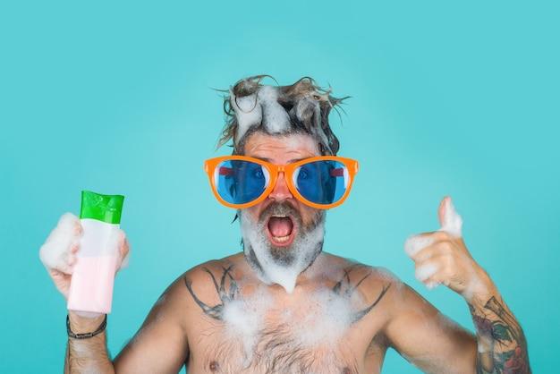 Head washing man in shower man holds shampoo bottle man with foam on head shampoo bottle bearded man