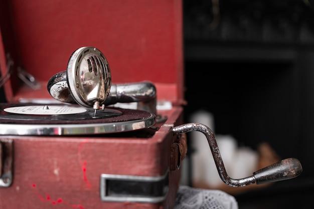 Голова с иглой граммофона в стиле ретро в старом винтажном стиле на крупном плане винилового диска