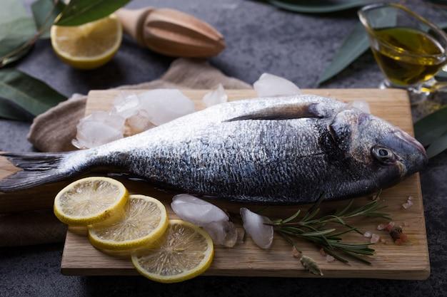 新鮮な魚のドラド。生のドラド魚と料理の材料。塩、ハーブ、コショウで新鮮な魚の金魚head。