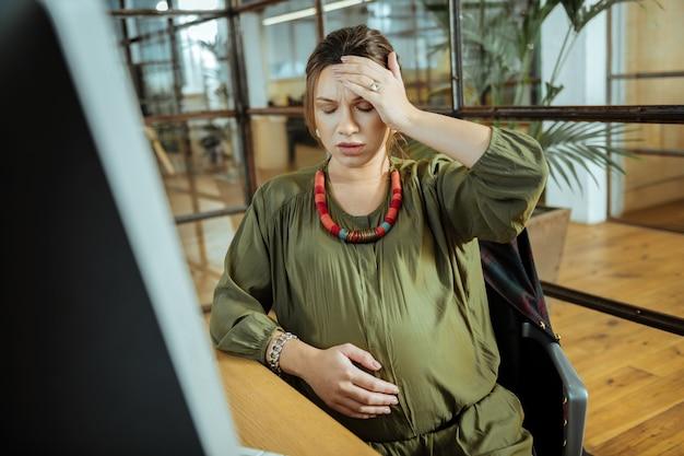 Головная боль после работы. молодая беременная женщина с головной болью после работы на компьютере