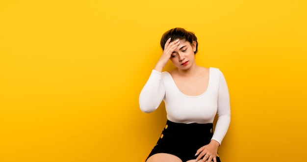 두통 외로운 배경에 있는 아시아 여성 고통과 편두통, 머리에 손으로 인해 필사적이고 스트레스가 많은 두통을 앓고 있습니다.