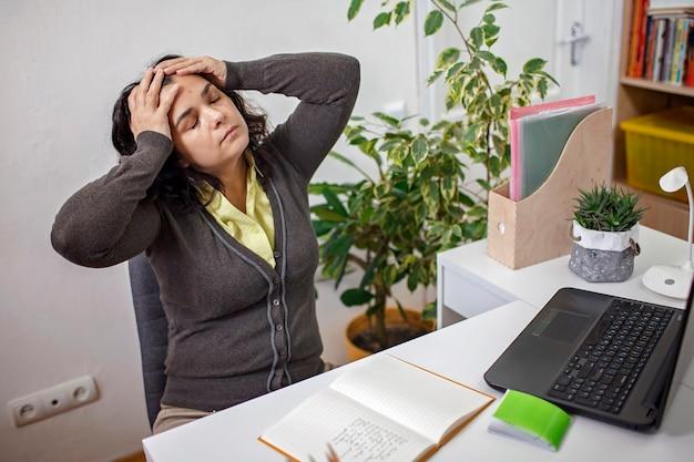 職場での頭痛。ラップトップコンピューターで働く女性