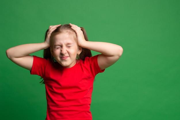 頭痛。赤いtシャツの頭をつかんで、緑のひどい痛みで顔をゆがめたブルネットの少女