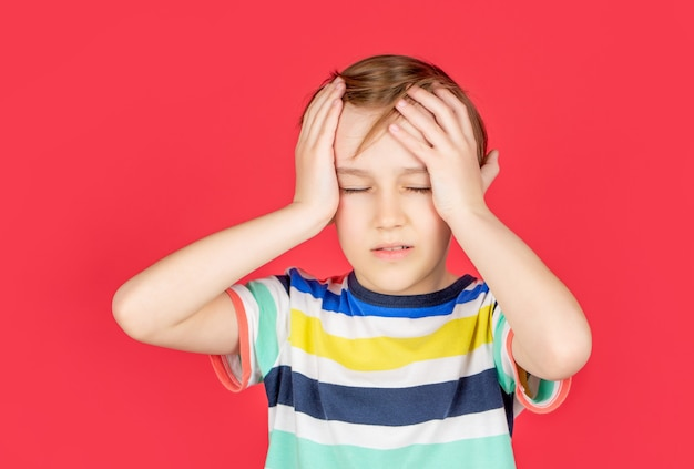 頭痛の子。片頭痛に苦しんでいます。ストレスによる頭痛。彼の手で頭を抱えて、赤い背景で隔離の悲しい少年の肖像画。頭痛のある少年。絶望、悲劇。