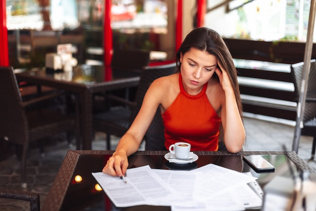 Headache. girl sitting in a cafe with a cup of coffee. working environment. mistakes disappointment